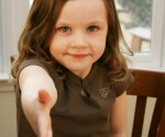 A young girl offers a handshake (focus on face)
