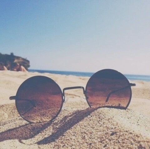 occhiali da sole con sabbia in spiaggia mare